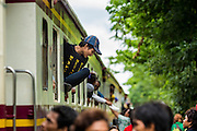 16 JUNE 2014 - ARANYAPRATHET, THAILAND: A Cambodian migrant returning to Cambodia jumps off a train at the end of the train line in Aranyaprathet, Thailand. More than 150,000 Cambodian migrant workers and their families have left Thailand since June 12. The exodus started when rumors circulated in the Cambodian migrant community that the Thai junta was going to crack down on undocumented workers. About 40,000 Cambodians were expected to return to Cambodia today. The mass exodus has stressed resources on both sides of the Thai/Cambodian border. The Cambodian town of Poipet has been over run with returning migrants. On the Thai side, in Aranyaprathet, the bus and train station has been flooded with Cambodians taking all of their possessions back to Cambodia. PHOTO BY JACK KURTZ