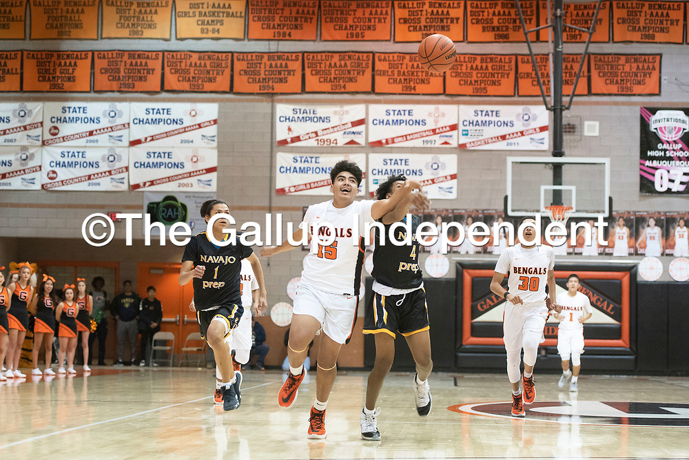 Gallup's Kody Touchine (15) and Navajo Prep's Dontrelle Denetso (4) try to gain possession of the ball Thursday, Jan. 2 at the Gallup Invitational boys basketball tournament at Gallup High School.