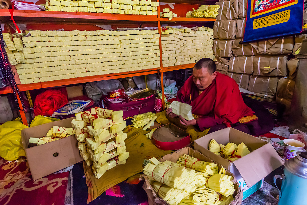 A monk packing incense in envelopes for donors, Tsurphu Monastery, Gurum, Tibet (Xizang), China.