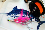 Layout of blue marlin flag with heavy fly reels and pink double hook popping fly.
