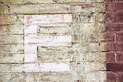 The letter 'E' painted on a deteriorating brick wall. Missoula Photographer