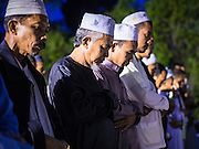 17 JUNE 2015 - YAHA, YALA, THAILAND:  People pray after the crescent moon was sighted and Ramadan started in Yaha, Thailand. Thousands of people came to Yaha District in Yala province of Thailand for the Hilal - the first sighting of the crescent moon that marks the official beginning of the Muslim holy month of Ramadan. Despite cloudy weather and intermittent rain showers, the moon was sighted and religious leaders declared the official beginning of Ramadan.   PHOTO BY JACK KURTZ