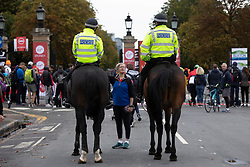 © Licensed to London News Pictures. 03/10/2021. London, UK. A woman talks to mounted police officers outside Greenwich Park ahead of the start of the London Marathon.This London Marathon will be the first full scale staging of the race in more than two years due to the Coronavirus Pandemic.  Photo credit: George Cracknell Wright/LNP