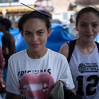 Two sisters from Honduras wait in line to wash at the El Chaparral camp for asylum seekers in Tijuana. Approximately 2000 people were living in the camp at the time of the photograph in July 2021. Five portaloos were provided by the municipality, they were also used as showers.