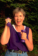 Woman age 56 doing an upper body workout.  Cedarville Michigan USA