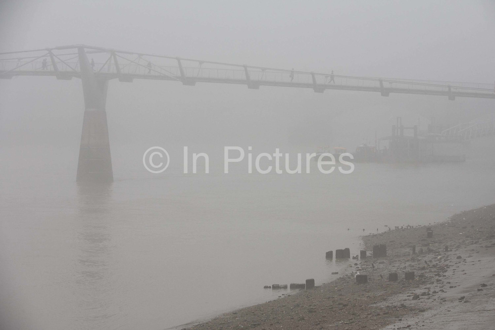 """Morning fog envelopes pedestrians and a jogger crossing the river Thames on the Millennium Bridge. It is mid-morning but the misty conditions have still to improve enough for visibility to allow a clear view a cross the river where city offices and skyscrapers are normally seen. In the foreground are old wooden posts that once formed jetties and landing stages on what was once a very busy waterway in the capital. London's Millennium Footbridge is a steel suspension bridge for pedestrians linking Bankside with the City of London. Construction began in 1998 and it initially opened in June 2000. Londoners nicknamed the bridge the """"Wobbly Bridge"""" after pedestrians initially felt an unexpected swaying motion."""