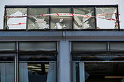 """Birmingham, United Kingdom, June 14, 2021: A tape says """"War Crime Scene"""" placed by the Palestine Action activist who appears to be using a sledgehammer to break the windows of an admin office facility owned by Arconic industrial manufacturer in Birmingham on Monday, June 14, 2021 - after they 'occupied the site claiming the company 'provided cladding for Grenfell Tower' and 'materials for Israel's fighter jets.' (Photo by Vudi Xhymshiti)"""
