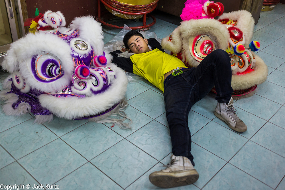 09 FEBRUARY 2014 - HAT YAI, SONGKHLA, THAILAND: A member of a lion dance troupe sleeps between heads stored in the office during Lunar New Year in the Tong Sia Siang Tueng temple in Hat Yai. Hat Yai was originally settled by Chinese immigrants and still has a large ethnic Chinese population. Chinese holidays, especially Lunar New Year (Tet) and the Vegetarian Festival are important citywide holidays.     PHOTO BY JACK KURTZ