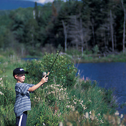 Randolph, NH..A young boy tries his luck at fishing on a beaver pond in New Hampshire's White Mountains.