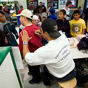 Jordin Tootoo grew up in a small village along the Hudson Bay only a hundred miles from the Arctic Circle. The first Inuit to play professionally in the National Hockey League, Tootoo is close to his family and friends to nearly everyone in Rankins Inlet in Northeast Canada, as is evident at a memorabilia signing at the local market. <br /> <br /> Image available for licensing and for a personal print. Please Add To Cart and select the size and finish. All prints are delivered directly to you from the printer.