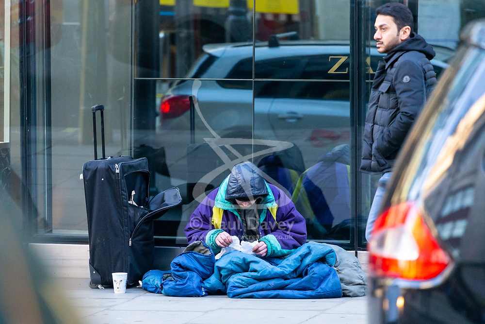 Wrapped up against the cold a homeless man eats from a paper bag as Eastern European beggars and street performers take advantage of the UK's relative wealth, squeezing opportunities for the UK's own homeless. London, December 13 2018.