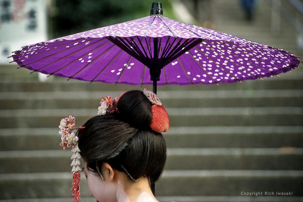 Detail view of a maiko (apprentice geisha) with an umbrella near Kiyomizu-dera (temple) in Kyoto, Kyoto Prefecture, Japan.