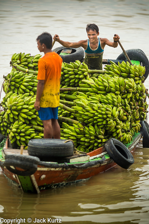 """10 JUNE 2014 - YANGON, MYANMAR:   A banana boat comes to the jetty in Yangon. The """"banana jetty"""" is on the Yangon River north of central Yangon on Strand Road. Bananas, coconuts and other fruit are brought in here from upcountry, sold and reshipped to other parts of Myanmar (Burma). All of the labor here is done by hand. Porters carry the produce to the jetty and porters load the boats before they steam upriver.   PHOTO BY JACK KURTZ"""