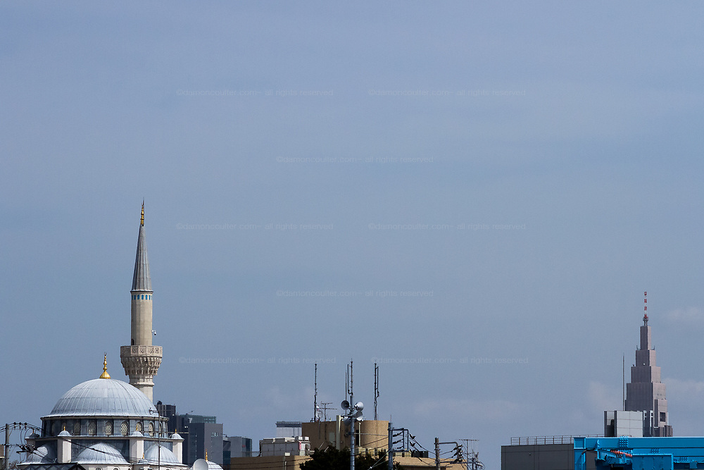 The dome and minaret of the Tokyo Camii Mosque (left) with the Docomo Tower behind. Yoyogi-Uehara, Tokyo, Japan. Friday March 22nd 2019.   The Tokyo Camii Mosque is the largest mosque in Japan where estimate currently put the immigrant and native population of Muslims at around 130,000.