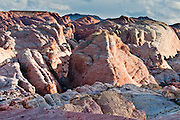 Sunset light illuminates colorful orange, pink, yellow, and white sandstone in White Domes area of Valley of Fire State Park, Nevada, USA. Starting more than 150 million years ago, great shifting sand dunes during the age of dinosaurs were compressed, uplifting, faulted, and eroded to form the park's fiery red sandstone formations. The park also boasts fascinating patterns in limestone, shale, and conglomerate rock. The park adjoins Lake Mead National Recreation Area at the Virgin River confluence, at an elevation of 2000 to 2600 feet (610-790 m), 50 miles (80 km) northeast of Las Vegas, USA. Park entry from Interstate 15 passes through the Moapa Indian Reservation.