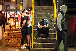 © Licensed to London News Pictures . 28/10/2018. Manchester, UK. Two men kiss by a stairway as a third sits on stairs with his head in his hands . Revellers on a night out , many in fancy dress , on the weekend before Halloween . Photo credit: Joel Goodman/LNP
