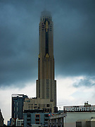 "16 SEPTEMBER 2015 - BANGKOK, THAILAND: The top of Baiyoke Tower II is obscured by clouds during a rain storm in Bangkok. It's 304 meters (997 feet) tall and the tallest skyscraper in Bangkok. It has a hotel with more than 600 rooms and a rooftop observation deck.  The remnants of tropical storm ""Vamco"" hit Bangkok Wednesday. Storm, downgraded to a tropical depression, brought bands of rain to central Thailand, including Bangkok. The Thai Meteorological Department said the storm would help alleviate the drought that has gripped Thailand since late last year.     PHOTO BY JACK KURTZ"