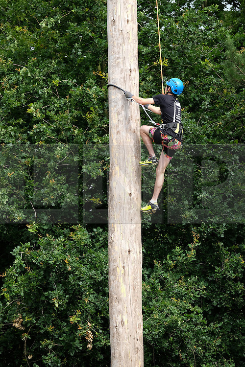 © Licensed to London News Pictures.14/07/15<br /> Harrogate, UK. <br /> <br /> A pole climber races to the top of an 80ft pole during a times event on the opening day of the Great Yorkshire Show.  <br /> <br /> England's premier agricultural show opened it's gates today for the start of three days of showcasing the best in British farming and the countryside.<br /> <br /> The event, which attracts over 130,000 visitors each year displays the cream of the country's livestock and offers numerous displays and events giving the chance for visitors to see many different countryside activities.<br /> <br /> Photo credit : Ian Forsyth/LNP