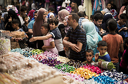 June 14, 2018 - Gaza City - Palestinians shop in a market before the holiday of Eid al-Fitr in the Jabalia camp the northern Gaza Strip on June 14, 2018. Eid al-Fitr is the end of Ramadan for Muslims when believers refrain from eating, drinking, smoking and sexual activities from dawn until dusk. (Credit Image: © Mahmoud Issa/Quds Net News via ZUMA Wire)