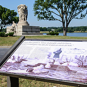 John Ericsson National Memorial with Sign. The John Ericsson National Memorial, on the bank of the Potomac River near the Lincoln Memorial, is a monument to Civil War naval engineer John Ericsson, the designer of the breakthrough iron-clad naval vessel USS Monitor. The memorial was designed by architect Albert Randolph Ross and sculpted by James Earle Fraser from the same pink granite used in the Lincoln Memorial. Because Ericsson was Swedish-born, the memorial consists of a combination of symbolic elements from his birthplace and his adopted homeland.