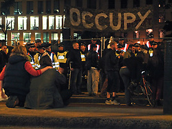 © licensed to London News Pictures. London, UK. 14/07/12. Actvists watch the clearance of the square take place. Enforcement officers clear the remaining 'Occupy' protest camp in London's Finsbury Square during the early hours of this morning after Islington Council won a High Court battle over the site. Photo credit: Jules Mattsson/LNP