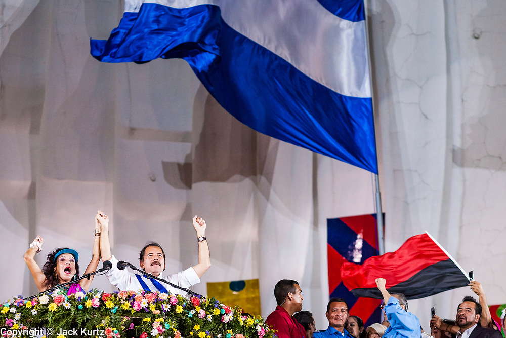 """10 JANUARY 2007 - MANAGUA, NICARAGUA:  ROSARIO MURILLO, left, wide of Nicaraguan President DANIEL ORTEGA, right, take the podium so Ortega can make his inaugural speech in Managua. Ortega, the leader of the Sandanista Front, was sworn in as the President of Nicaragua Wednesday. Ortega and the Sandanistas ruled Nicaragua from their victory of """"Tacho"""" Somoza in 1979 until their defeat by Violetta Chamorro in the 1990 election.  Photo by Jack Kurtz"""