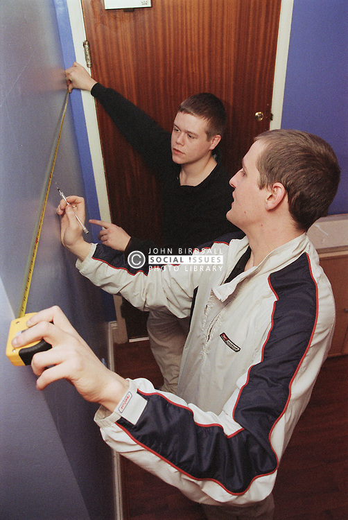 Two male residents of Young Persons' Resettlement hostel putting numeracy skills into practice during basic numeracy lesson,