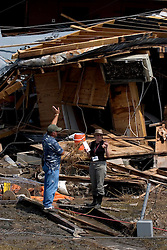 26 Sept, 2005. Cameron, Louisiana. Hurricane Rita aftermath. <br />  A FEMA official discusses the destruction to a journalist from Florida amidst the destroyed remains of downtown business in Cameron, Louisiana two days after the storm ravaged the small town.<br /> Photo; ©Charlie Varley/varleypix.com
