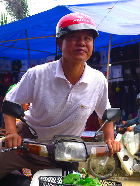 Vietnamese man mounting his scooter after shopping a rural market in Northern Vietnam
