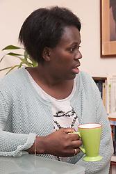 Woman in flat drinking tea.