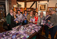 The Purple Finches knitting group donates purple hats to Janine Mitchell from New Hampshire Children's Trust Saturday morning at the Gilmanton Library.  (Karen Bobotas/for the Laconia Daily Sun)