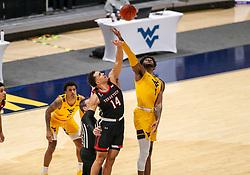 Jan 25, 2021; Morgantown, West Virginia, USA; Texas Tech Red Raiders forward Marcus Santos-Silva (14) and West Virginia Mountaineers forward Derek Culver (1) jump for the tip at WVU Coliseum. Mandatory Credit: Ben Queen-USA TODAY Sports