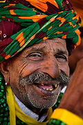 Traditional Rajasthani  flute player on the 20th January 2018  in the village of Shilpgram, Udaipur, India. The loss of front teeth gives room for the double flute to fit in! The individual villages each have their own distinctive turbans both in colours and the methods of tying.