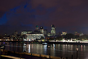 Night scene looking over the River Thames towards the skyline of the City of London financial district.