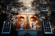 Old original entrance to St. John of Wapping school for boys and girls, Wapping, East London. Both sexes had separate entrances and were segregated. St John's Old School, Scandrett Street, Wapping. The school was founded in 1695, but the present building only dates back to 1756. On the front of the building are statues of two of the pupils in their traditional uniforms. Boys and girls were segregated in schools until the middle of the twentieth century, and used to enter the school buildings by separate entrances.
