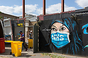 On the day that the UK death rate during the Coronavirus pandemic surpasses 40,000, including almost 10,000 care home residents, the highest rate in Europe, workmen clear a brownfield site next to a mural created by the anonymous street artist known as 'Artful Dodger' (after Charles Dickens's pickpocket character in Oliver Twist), of a Muslim NHS (National Heath Service) nurse wearing a surgical face mask, at Elephant & Castle in south London, on 121th May 2020, in London, England.