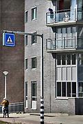 Nederland, Nijmegen, 4-4-2020  Twee mannen praten met elkaar terwijl de een op straat en de aner hoog op een balkon staat. Voorbeeld van contact  tussen oudere mensen met social distancing tijdens de coronacrisis.Foto: Flip Franssen
