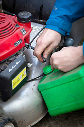 Lawnmower maintenance. Draining the petrol tank before storing over winter