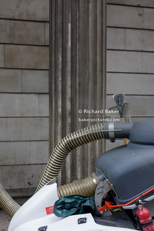 A corporation of London street cleaning hose with contactor Amey and a pillar of the Bank of England.