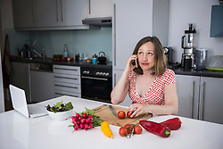 Pregnant woman talking on smartphone and sitting on chair with fresh vegetables in the kitchen, Munich, Bavaria, Germany
