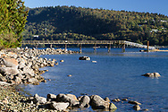 """A pier over Burrard Inlet at Cates Park (Whey-ah-Wichen) in North Vancouver, British Columbia, Canada.  Burnaby Mountain is in the background. Whey-ah-wichen is an ancestral village site and the Hun'qumyi'num place name means """"facing both directions"""" and """"facing the wind""""."""