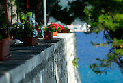 Detail of outer city wall with potted plants, sea in background. Korcula old town, island of Korcula, Croatia