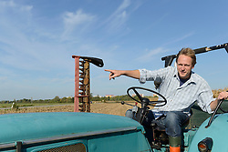 Farmer sitting on tractor and pointing somewhere, Bavaria, Germany
