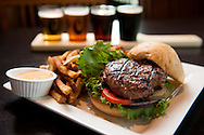 1 OCT. 2015 -- MARYLAND HEIGHTS, Mo. -- A featured item on the menu at O'Bar, the bar and restaurant at the O'Fallon Brewery's Maryland Heights facility, is the O'Bar Premium Burger, made with beef from Italian Piedmontese cattle fed O'Fallon spent grain, served with lettuce, Roma tomato, homemade pickle, and red onion, photographed at the restaurant Thursday, Oct. 1, 2015. The burger can be ordered with a flight of beers, including O'Fallon Kite Tail, O'Fallon Gold, O'Fallon Cherry Chocolate and O'Fallon King Louie Stout. Photo © copyright 2015 Sid Hastings.