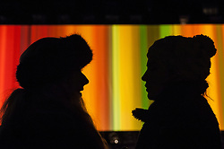 """© Licensed to London News Pictures. 15/01/2016. London, UK.  Visitors silhouetted against """"Spinning Light in Living Colour"""" by Elaine Buckholtz on display in Grosvenor Square.  The work forms part of Lumiere London, a major new light festival which is into the second of four evenings and featuring artists who work with light.  The event is produced by Artichoke and supported by the Mayor of London.  Photo credit : Stephen Chung/LNP"""