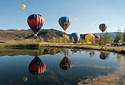 Hot air balloons float over pond, Snowmass Balloon Festival, Colorado Sept. 18-20, 2009