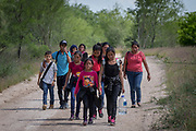 Central American asylum seekers who illegally crossed the Mexico-U.S. border walk up a dirt road near Mission, Texas, U.S., May 9, 2018.