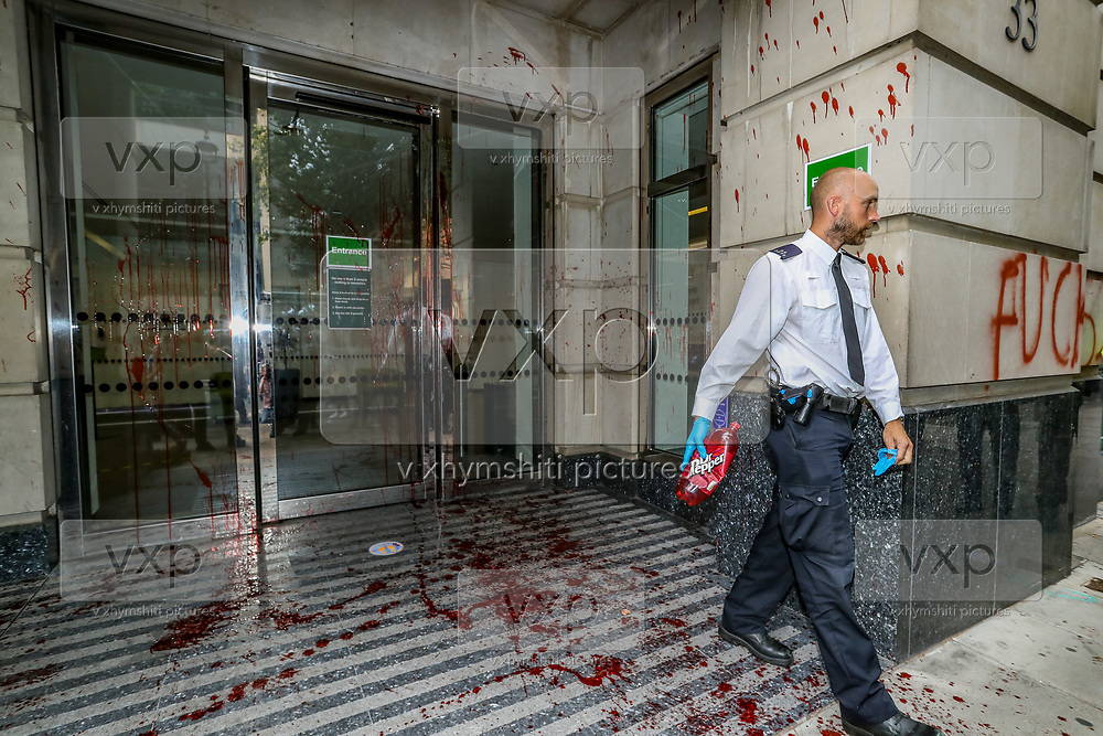 A police officer inspects entrance of Department for Transport after a group of Extinction Rebellion activists pelted it in red colour, while some others glued themselves outside DPT in central London on Friday, Sept 4, 2020. Police closed Horseferry Road both ways as a group of protestors from Parliament Square marched towards Department for Transport demanding an end of HS2 construction. Environmental nonviolent activists group Extinction Rebellion enters its 4th day of continuous ten days protests to disrupt political institutions throughout peaceful actions swarming central London into a standoff, demanding that central government obeys and delivers Climate Emergency bill. (VXP Photo/ Vudi Xhymshiti)