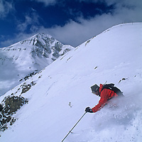 Skiing, Big Sky, Montana.  Tom Jungst skis out of bounds off Challenger Lift, with Lone Mountain in background.