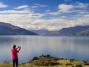 A woman photographs Lake Wakatipu, one of New Zealand's most beautiful lakes, surrounded by mountains and set off by clouds and blue sky on an autumn day.